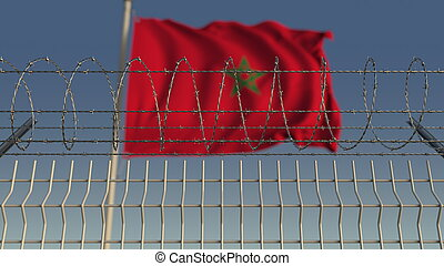 Defocused waving flag of Morocco behind barbed wire fence. ...