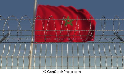 Defocused waving flag of Morocco behind barbed wire fence....