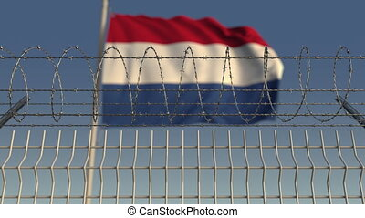 Defocused waving flag of Netherlands behind barbed wire...