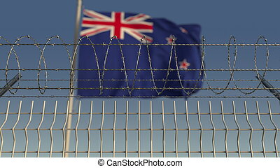 Defocused waving flag of New Zealand behind barbed wire fence. 3D rendering