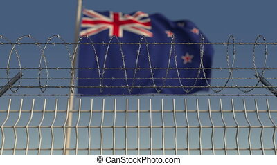 Defocused waving flag of New Zealand behind barbed wire...
