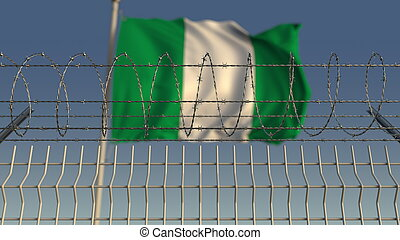 Defocused waving flag of Nigeria behind barbed wire fence. 3D rendering