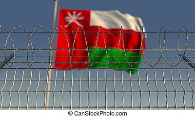 Defocused waving flag of Oman behind barbed wire fence. 3D rendering