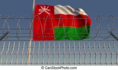 Defocused waving flag of Oman behind barbed wire fence. Loopable 3D animation