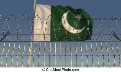 Defocused waving flag of Pakistan behind barbed wire fence....