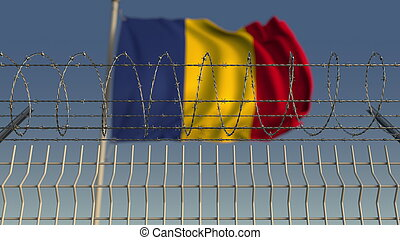 Defocused waving flag of Romania behind barbed wire fence. ...