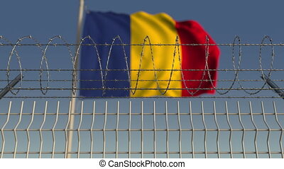 Defocused waving flag of Romania behind barbed wire fence....