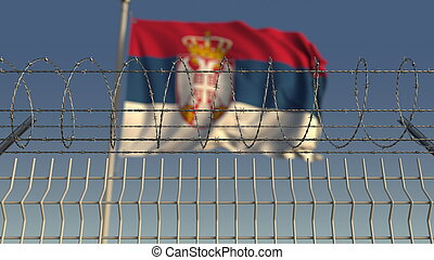Defocused waving flag of Serbia behind barbed wire fence. 3D rendering