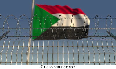 Defocused waving flag of Sudan behind barbed wire fence....