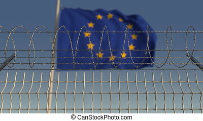 Defocused waving flag of the European Union EU behind barbed...