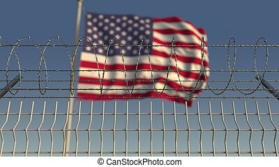 Defocused waving flag of the United States behind barbed ...