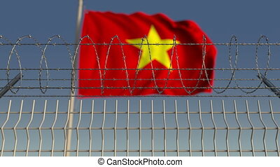 Defocused waving flag of Vietnam behind barbed wire fence....