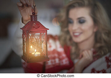 Defocused woman carrying a lantern