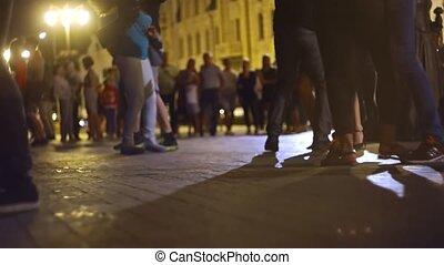 Defocused young couples dancing salsa open-air in slow...