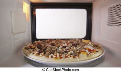 Defrosting raw frozen seafood pizza in the microwave oven inside view