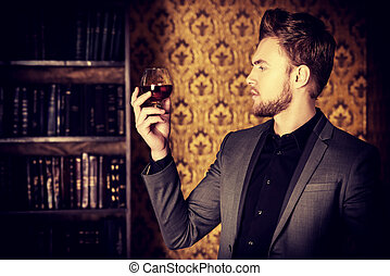 degustation - Elegant man in a suit with glass of beverage ...