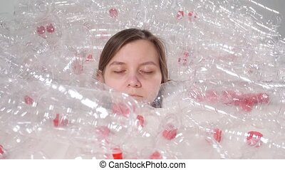 Dehydrated sick woman is lying in a pile of plastic bottles. Environmental pollution problem. Stop nature garbage environment protection concept indoors
