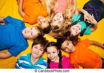 deitando, círculo, crianças, grupo, feliz