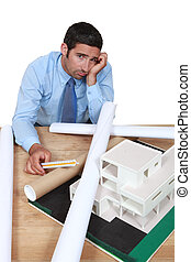 Dejected architect sitting at his desk