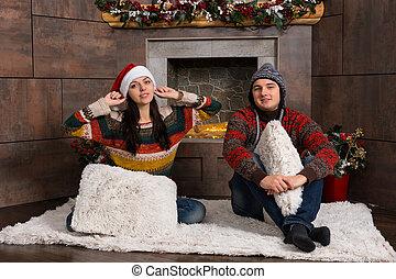 dekorerat, par, vinter, sittande, ung, rolig, främre del, matta, eldstad, hattar