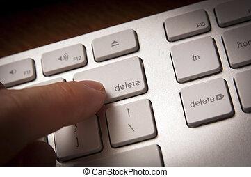 Delete Key - Finger pressing delete key with moody lighting...