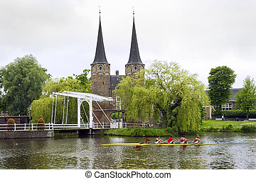 Delft Rowing - A rowing team in a coxed four rowing past a...