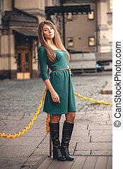 delgado, mujer, en, vestido verde, posar, en, viejo, calle