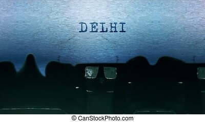 delhi words Typing on a sheet of paper with an old vintage typewriter.
