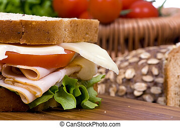 A fresh deli sandwich with tomatoes swiss cheese, lettuce and lots of meat.