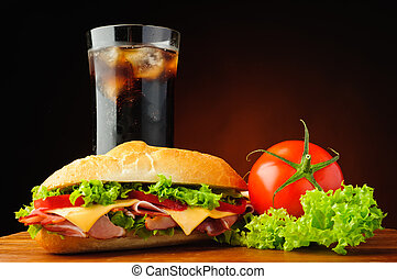 still life with deli sub sandwich, fresh vegetables and cola soft drink