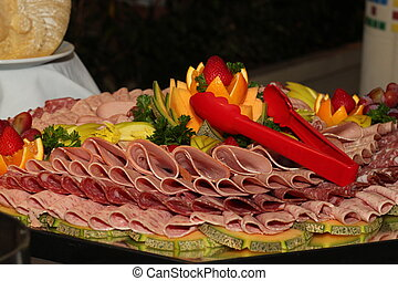 A tray of sliced deli meats on a buffet table