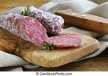 delicacy smoked sausage (pepperoni) on a cutting board