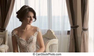 Delicate and elegant bride sitting in the chair in the apartments