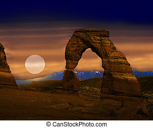 The moon shines through an evening haze shortly after sunset at Delicate Arch in Arches National Park, UT.
