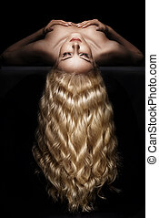 Delicate blond lady with long, wavy hairstyle