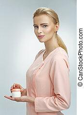 Delicate blond scientist presenting a skin cream