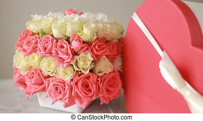 delicate bouquet of pink and white roses . box with a gift in the form of heart