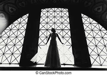 Delicate bride's silhouette illuminated by the light from a window