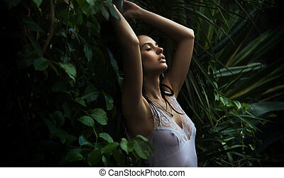 Delicate brunette posing in a forest