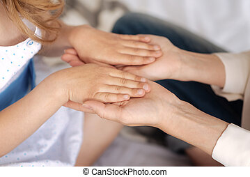 Delicate female hands holding hands of child