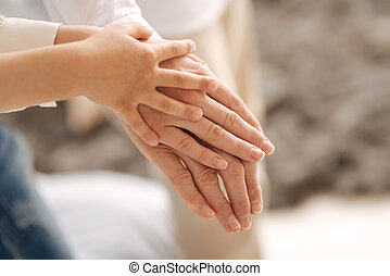 Delicate female hands of three generations