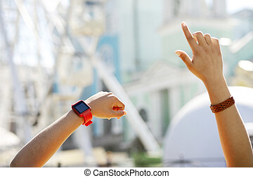 Delicate female hands with smart watch thrown in the air