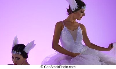Delicate feminine ballerinas in a white swan costume posing on top of a cake decorated with flowers. Two young women gracefully moves in slow motion on a pink background in the studio. Close up
