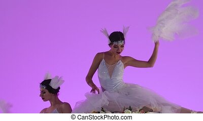 Delicate feminine ballerinas in a white swan costume posing on top of a cake decorated with flowers. Two young women gracefully moves in slow motion on a pink background in the studio. Festive theatrical dance show. Close up.