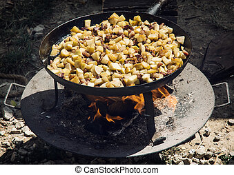 Delicate fried bacon with apples on metal pan