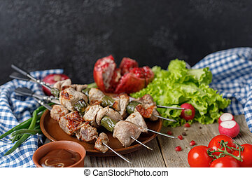Delicate kebabs of pork on skewers lined with a dish of fresh vegetables and ripe pomegranate. Meat cooked on an open fire. Still life on a wooden background with textiles. Close-up.
