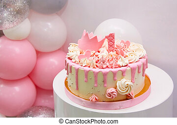 delicate pink cake with baubles, golden princess crown and number 1. One year old girl first birthday party with cake and helium balloons on white background with place for text