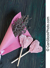 Delicate pink marshmallows in the shape of a heart on a stick. Several pieces lie on brushed pine boards. Nearby is a bouquet of lavender in a pink paper bag.