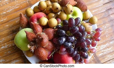Delicious and arranged tropical fruit in bowl on a wooden...