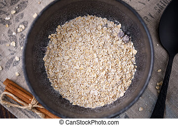 Delicious and healthy breakfast. A bowl with dry flakes of oatmeal.
